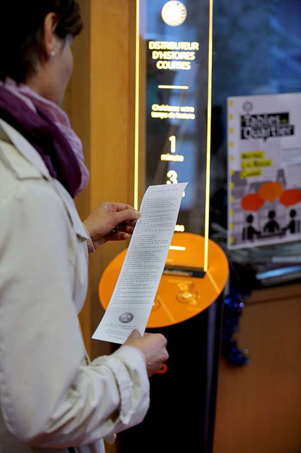 A woman reads a short story at a short-story distribution terminal in the Mistral district of Grenoble, on October 12, 2015. The city of Grenoble is testing the invention of a local start-up and recently installed the terminal, which delivers free reading material to people waiting in public spaces.  AFP PHOTO / JEAN-PERRE CLATOT